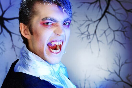 Portrait of a handsome young man with vampire style make-up. Sho